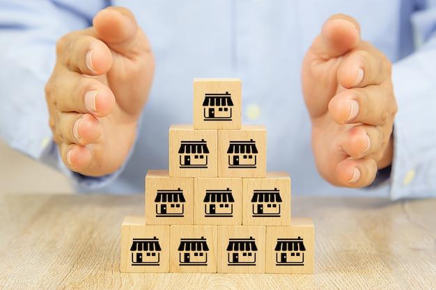Les mains protègent les blocs de bois empilés avec l'icône de marketing de franchise.