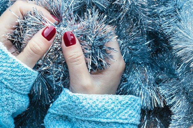 Mains en pull tricoté avec des clous bordeaux sur fond de guirlande de guirlandes de noël argent