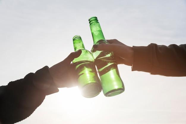Mains qui claquent des bouteilles de bière