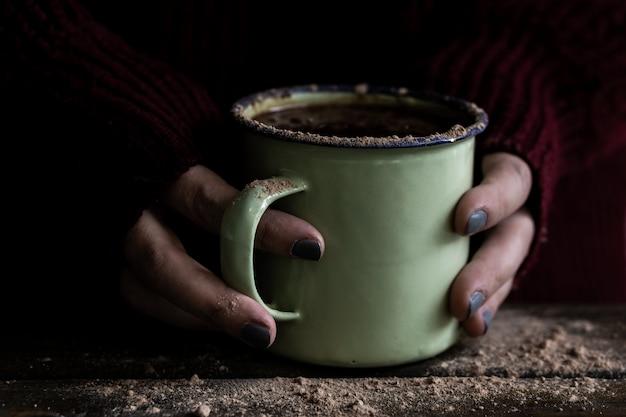 Mains ramasser une tasse de chocolat chaud