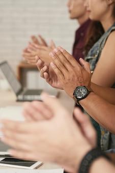 Les mains recadrées d'un groupe de personnes qui se reposent pour motiver le conférencier
