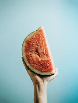 Mains saisissant une tranche de pastèque vue de dessus maquette avec copie espace concept d'été