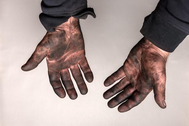 Mains sales dans la voiture masut (huile noire) sur mur gris.