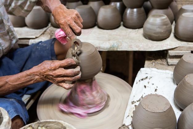 Mains sales faisant de la poterie dans l'argile sur la roue
