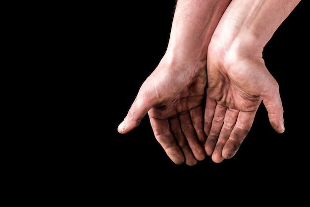 Mains sales isolés sur fond noir. mendiant les mains.