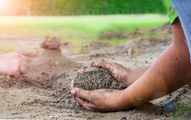 Les mains sales d'un petit garçon creusent dans la boue humide