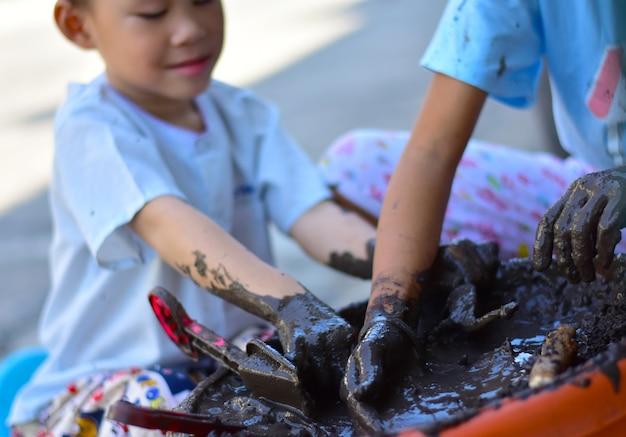Les mains sales d'un petit garçon creusent dans la boue mouillée