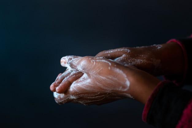 Mains savonnées d'une personne - importance de se laver les mains pendant la pandémie de coronavirus
