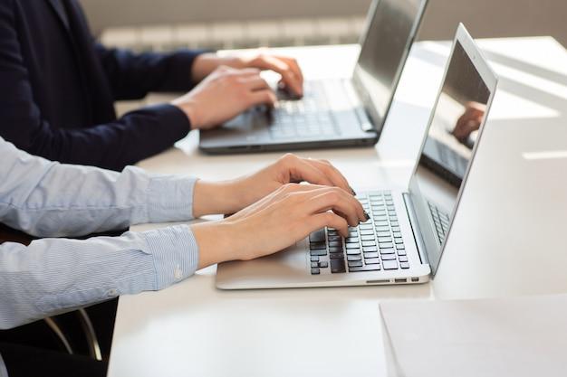 Les mains se bouchent, travaillant sur un ordinateur avec un document d'entreprise