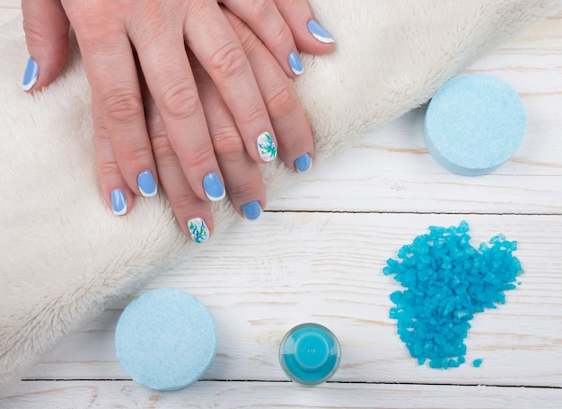 Mains sur une serviette, sel de bain et une bouteille de vernis à ongles