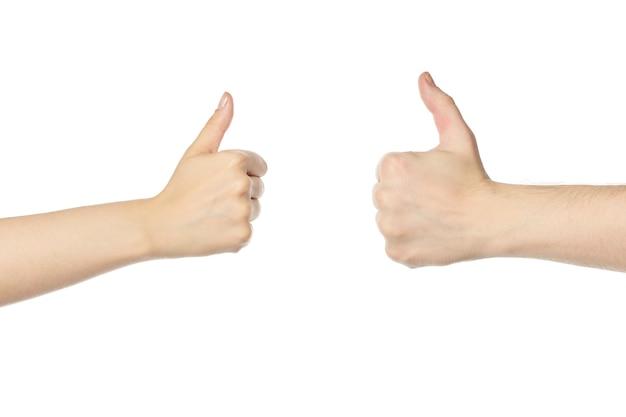 Mains avec signal de pouce vers le haut. mains d'homme et de femme comme symbole, fond blanc isolé. confirmation du super geste.