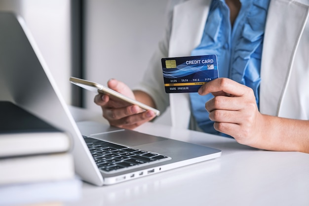 Mains sur smartphone, carte de crédit et dactylographie sur ordinateur portable pour les achats en ligne et les achats avec paiement