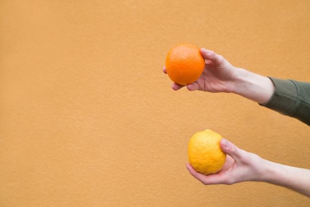 Les mains de son mari tiennent un citron et une orange sur le mur d'un mur orange. fruit du concept.