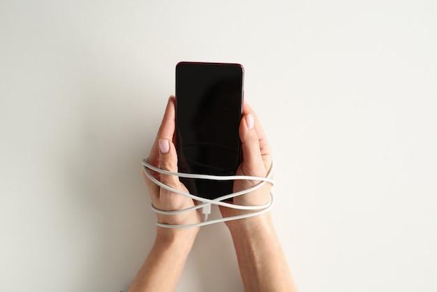 Les mains sont liées avec du fil et tiennent le smartphone. concept de dépendance au téléphone mobile