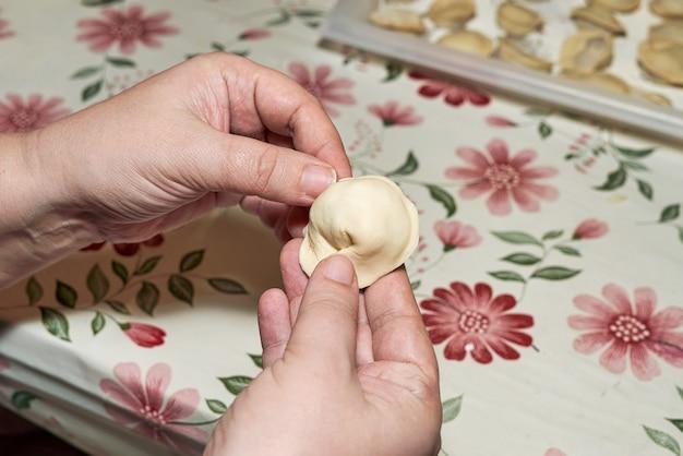 Les mains souillées de farine tiennent une boulette crue. cuire des boulettes faites maison