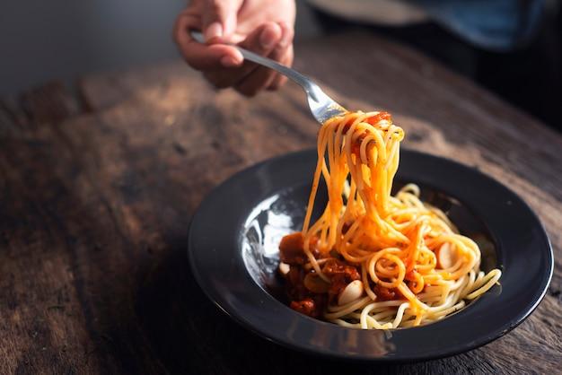 Des mains soulèvent une cuillère à spaghetti