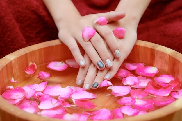 Mains spa manucure dans un bol en bois avec des pétales de rose