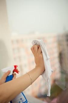Mains avec spray nettoyant la fenêtre
