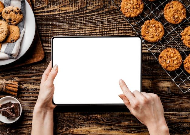 Mains avec tablette et délicieux biscuits à côté