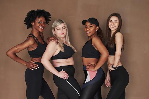 Les mains sur la taille. groupe de femmes multiethniques debout contre l'espace brun