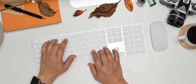 Mains tapant sur un clavier d'ordinateur sans fil sur un bureau blanc avec appareil photo, papeterie et décorations