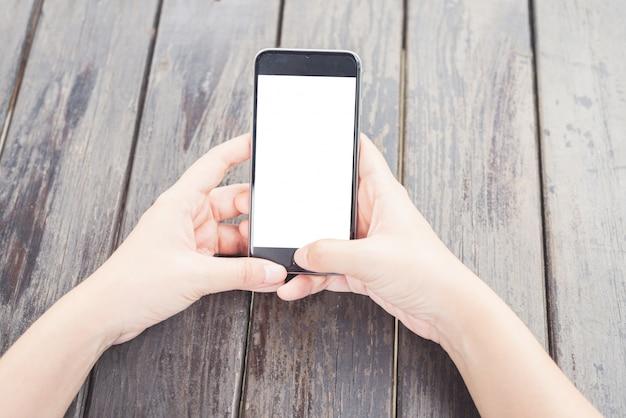 Mains tapant sur un téléphone mobile écran blanc
