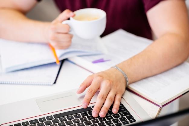 Mains avec une tasse et un ordinateur portable sur la table