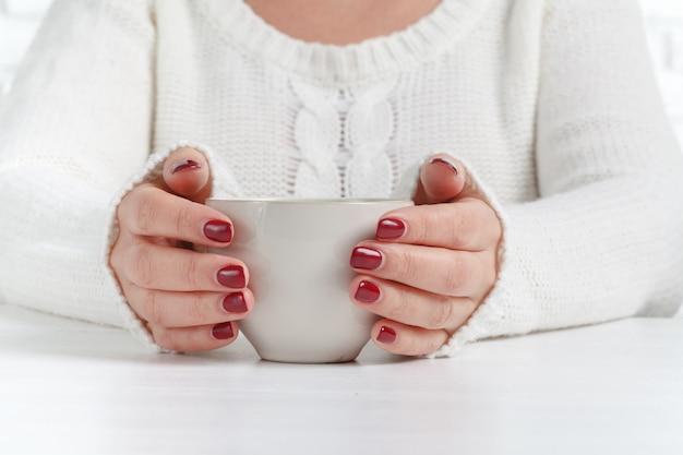 Mains avec une tasse de thé