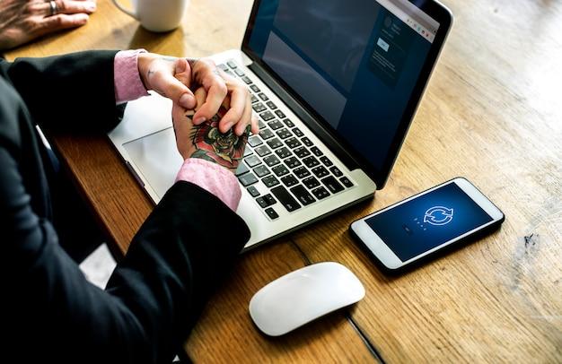 Mains avec tatouage sur ordinateur portable et souris