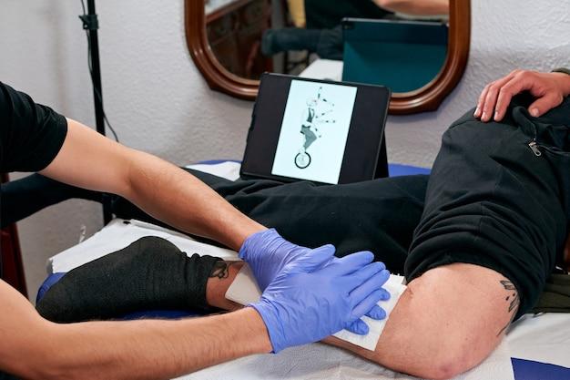 Les mains d'un tatoueur en gants bleus nettoyant le tatouage nouvellement terminé sur la jambe d'un homme