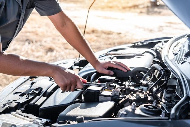 Mains de technicien de mécanicien automobile dans le service et l'entretien de réparation automobile