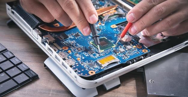 Mains de technicien vérifiant la carte mère avec le multimètre.