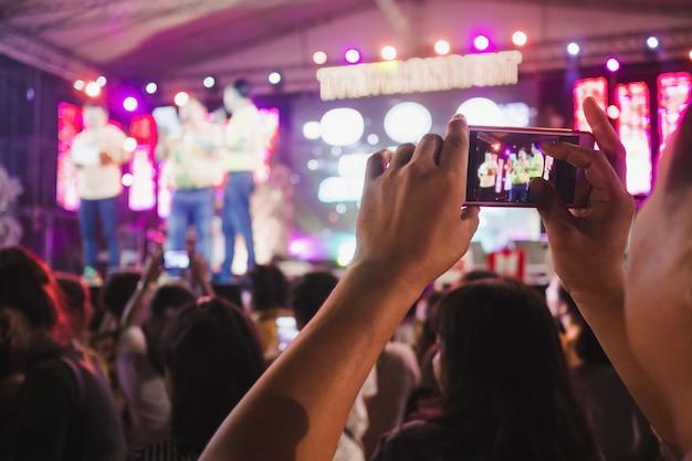 Mains avec téléphone intelligent enregistrant et prenant une photo