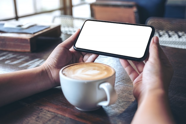 Mains tenant et à l'aide d'un téléphone mobile noir avec écran blanc horizontalement pour regarder avec une tasse de café sur une table en bois