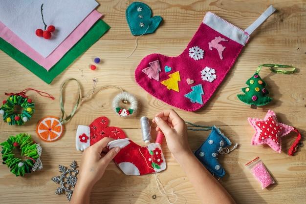 Mains tenant l'aiguille et la couture chaussette de noël en feutre pour la décoration de noël et du nouvel an