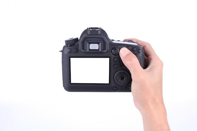 Mains tenant l'appareil photo reflex numérique sur fond blanc