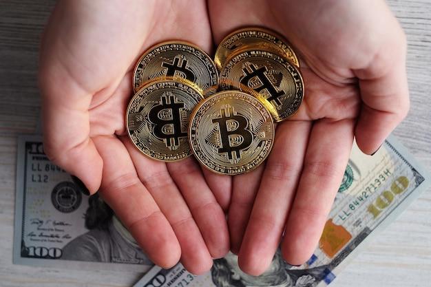 Mains tenant de l'argent virtuel bitcoins d'or.