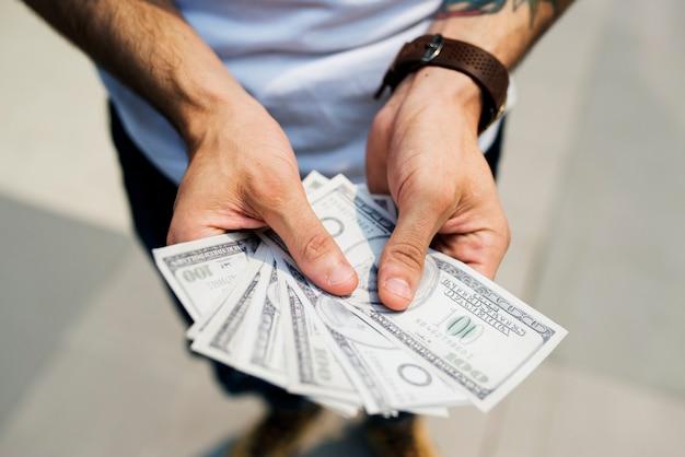 Mains tenant un billet d'un dollar