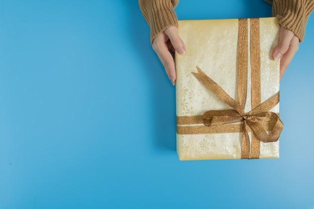 Mains tenant une boîte cadeau attachée avec un ruban marron sur bleu