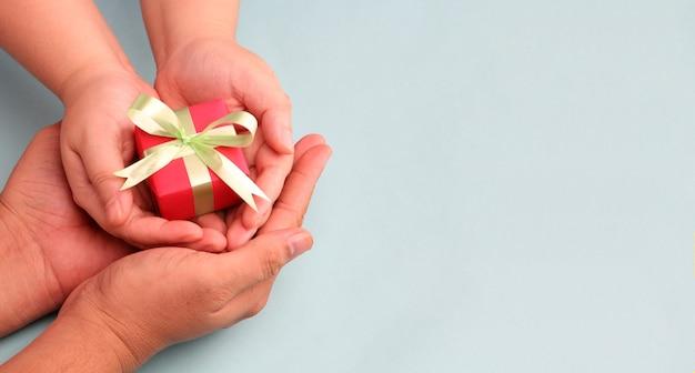 Mains tenant la boîte-cadeau sur fond bleu avec espace de copie.