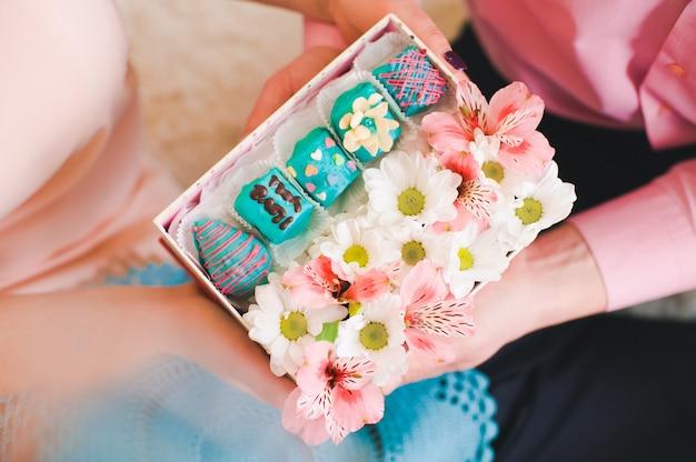 Mains tenant une boîte-cadeau remplie de fleurs et de bonbons aux fruits