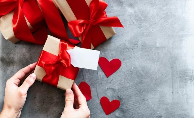 Mains tenant une boîte cadeau avec ruban rouge.