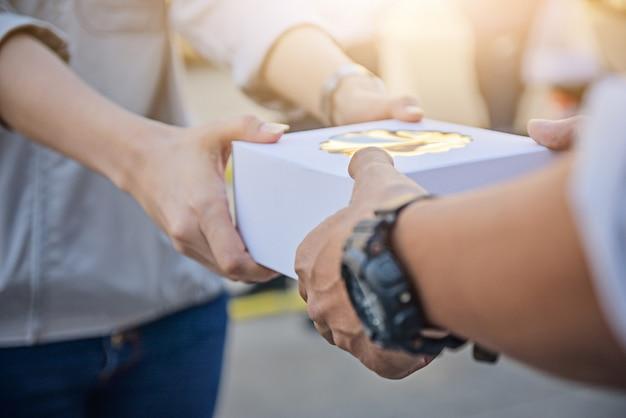 Mains tenant la boîte-cadeau