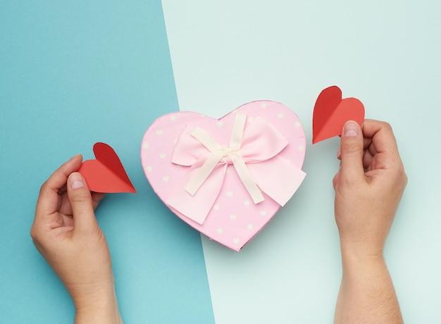 Mains tenant une boîte en carton rose avec un arc