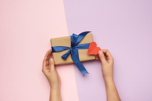 Mains tenant une boîte de papier cadeau