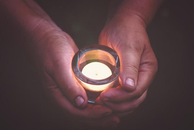 Mains tenant une bougie allumée dans l'obscurité, concept de prière et de spiritualité