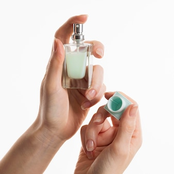 Mains tenant une bouteille de parfum