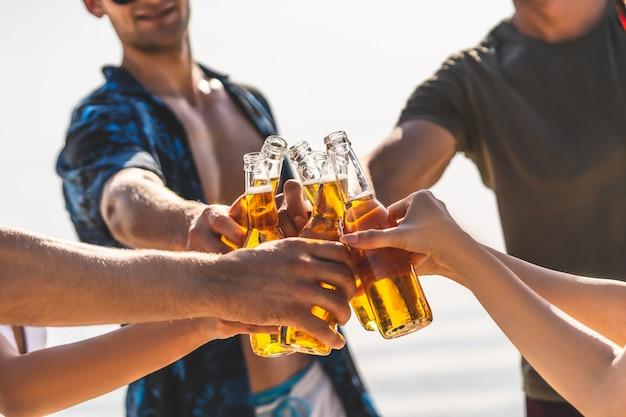 Les mains tenant des bouteilles de bière et faisant des acclamations