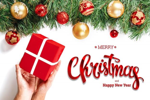 Mains tenant un cadeau, inscription joyeux noël et épinette verte sur un blanc. carte de noël, fond festif. technique mixte.