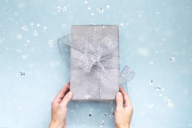 Mains tenant un cadeau de noël enveloppé d'un ruban d'argent sur bleu clair